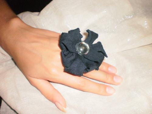 anel com flor de trapilho e pedra no centro